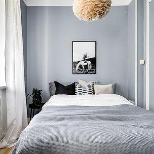 Inredning av ett minimalistiskt litet sovrum, med grå väggar, ljust trägolv och beiget golv