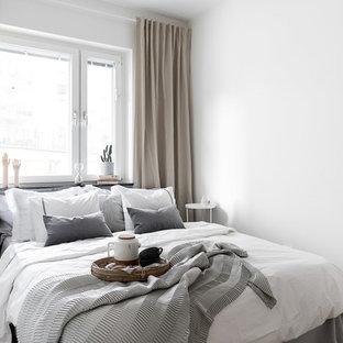Nordisk inredning av ett huvudsovrum, med vita väggar, ljust trägolv och beiget golv
