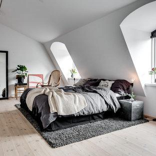 Inredning av ett skandinaviskt mellanstort huvudsovrum, med vita väggar och ljust trägolv