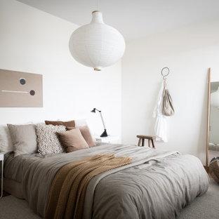 Idéer för skandinaviska huvudsovrum, med vita väggar och ljust trägolv