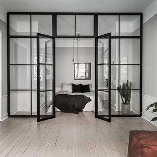 Idée de décoration pour une grand chambre parentale nordique avec un mur gris, un sol en bois clair et aucune cheminée.