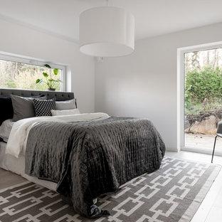 Minimalistisk inredning av ett mellanstort huvudsovrum, med laminatgolv, grått golv och vita väggar