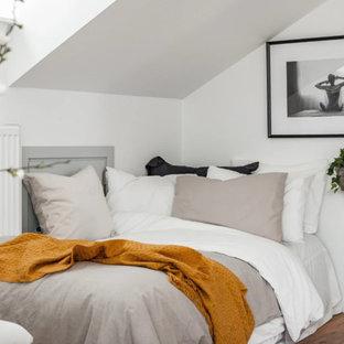 Inspiration för ett litet nordiskt huvudsovrum, med vita väggar, brunt golv och mellanmörkt trägolv