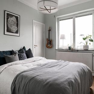 Idéer för ett nordiskt sovrum, med grå väggar, mellanmörkt trägolv och beiget golv