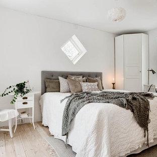 Foto på ett mellanstort minimalistiskt sovrum, med vita väggar, ljust trägolv och beiget golv