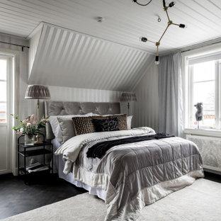 Inredning av ett nordiskt sovrum, med grå väggar, mörkt trägolv och brunt golv