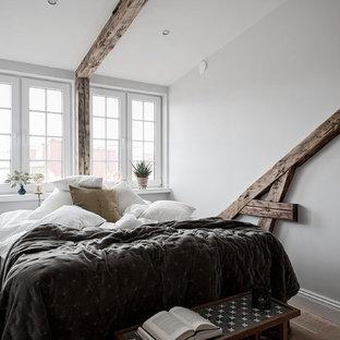 Idéer för att renovera ett litet minimalistiskt huvudsovrum, med vita väggar, mellanmörkt trägolv och brunt golv
