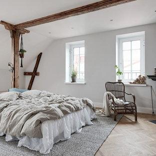 Nordisk inredning av ett stort huvudsovrum, med vita väggar, en öppen vedspis, en spiselkrans i trä, beiget golv och ljust trägolv