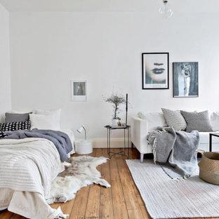 Exempel på ett nordiskt sovrum, med vita väggar och mellanmörkt trägolv