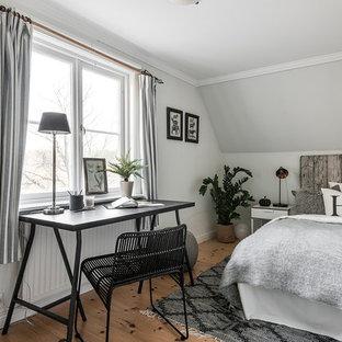 Nordisk inredning av ett litet sovrum, med vita väggar och ljust trägolv