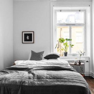Minimalistisk inredning av ett sovrum, med vita väggar, mörkt trägolv och brunt golv