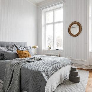 Idéer för nordiska huvudsovrum, med vita väggar och mellanmörkt trägolv