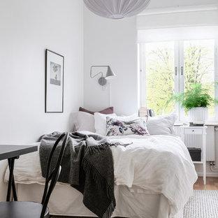 Bild på ett nordiskt sovrum, med vita väggar, mellanmörkt trägolv och brunt golv