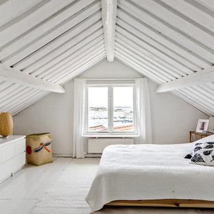 Exempel på ett maritimt sovrum, med vita väggar, ljust trägolv och vitt golv