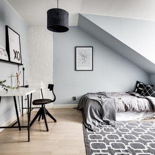Idéer för att renovera ett minimalistiskt gästrum, med blå väggar, ljust trägolv och beiget golv