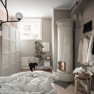 Bild på ett litet skandinaviskt sovrum, med grå väggar, ljust trägolv, beiget golv, en öppen hörnspis och en spiselkrans i trä