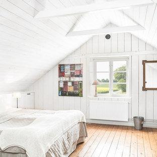 Bild på ett lantligt sovrum, med vita väggar och mellanmörkt trägolv