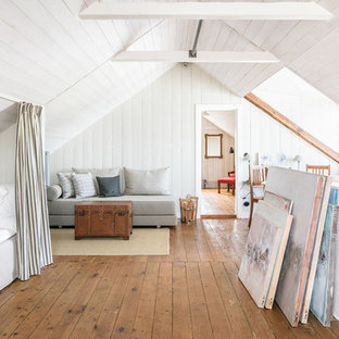 Design ideas for a country guest bedroom in Malmo with white walls, medium hardwood floors and brown floor.