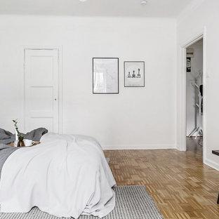 Idéer för att renovera ett minimalistiskt sovrum, med vita väggar, mellanmörkt trägolv och brunt golv
