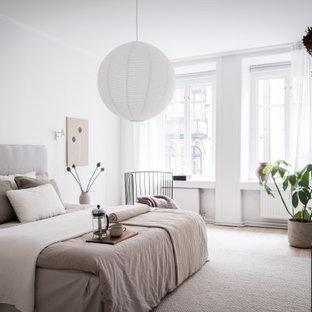 Bild på ett skandinaviskt sovrum, med vita väggar, ljust trägolv och beiget golv