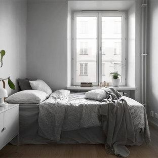 Foto på ett mellanstort minimalistiskt sovrum, med grå väggar och laminatgolv