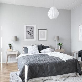 Idéer för ett skandinaviskt gästrum, med grå väggar, mellanmörkt trägolv och brunt golv