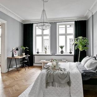 Foto på ett minimalistiskt huvudsovrum, med grå väggar, mellanmörkt trägolv och beiget golv