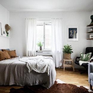 Idéer för att renovera ett litet nordiskt sovrum, med vita väggar, ljust trägolv och brunt golv