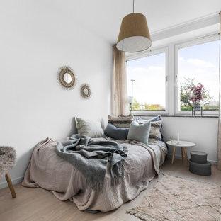 Idéer för ett skandinaviskt gästrum, med vita väggar och ljust trägolv