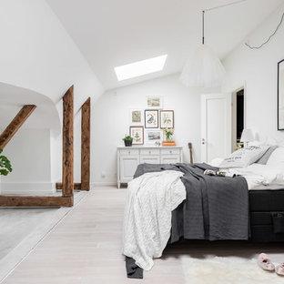 Skandinavisk inredning av ett mellanstort sovrum, med vita väggar och ljust trägolv