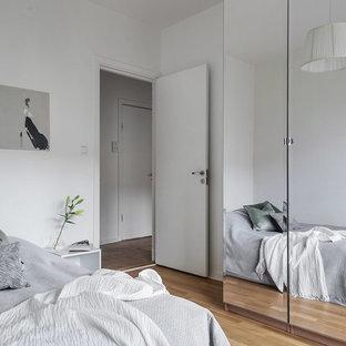 Inspiration för minimalistiska sovrum, med vita väggar, mellanmörkt trägolv och brunt golv