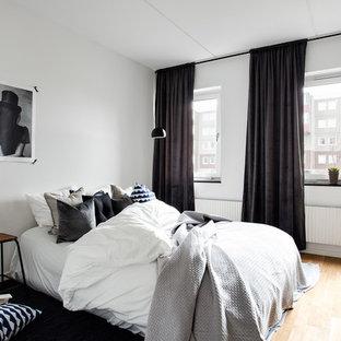 Exempel på ett skandinaviskt huvudsovrum, med vita väggar och ljust trägolv