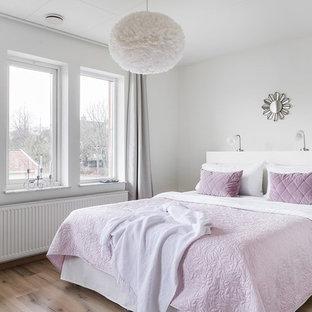 Bild på ett skandinaviskt sovrum, med vita väggar, mellanmörkt trägolv och brunt golv