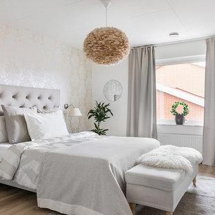 Modelo de dormitorio nórdico con paredes beige, suelo de madera en tonos medios y suelo marrón