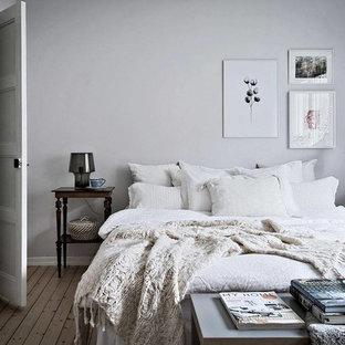 Minimalistisk inredning av ett stort huvudsovrum, med vita väggar och ljust trägolv