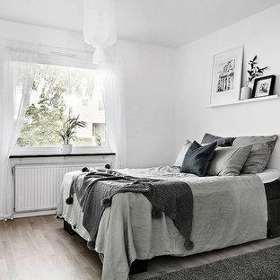 Idéer för att renovera ett stort skandinaviskt huvudsovrum, med vita väggar och ljust trägolv