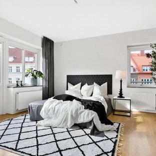 Idéer för att renovera ett minimalistiskt sovrum, med vita väggar, ljust trägolv och beiget golv