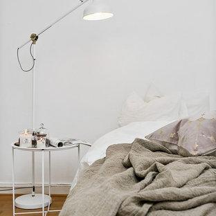 Idéer för skandinaviska sovrum, med vita väggar, mellanmörkt trägolv och beiget golv