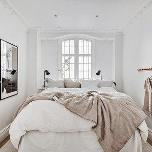 Minimalistisk inredning av ett litet huvudsovrum, med vita väggar, mörkt trägolv och brunt golv