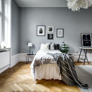 Exempel på ett nordiskt sovrum, med grå väggar, mellanmörkt trägolv och beiget golv
