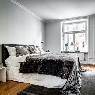 Inspiration för ett minimalistiskt sovrum, med grå väggar, mellanmörkt trägolv och brunt golv