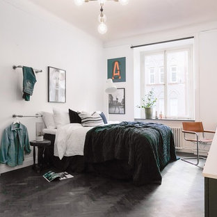 This is an example of a large scandi bedroom in Stockholm with white walls, plywood flooring, no fireplace and black floors.