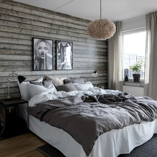 This is an example of a large scandinavian master bedroom in Stockholm with white walls, light hardwood floors, no fireplace and brown floor.
