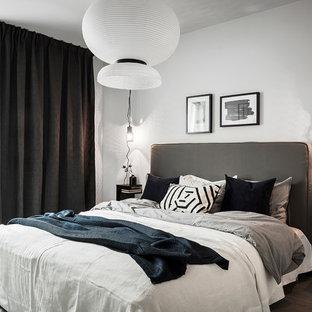Nordisk inredning av ett stort huvudsovrum, med vita väggar, ljust trägolv och grått golv