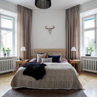 Idéer för att renovera ett stort nordiskt huvudsovrum, med vita väggar och ljust trägolv