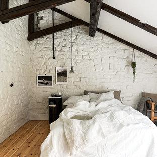 Inredning av ett nordiskt stort huvudsovrum, med vita väggar och ljust trägolv