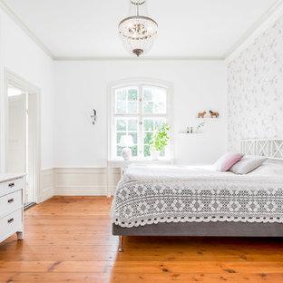 Foto de dormitorio campestre con paredes blancas, suelo de madera en tonos medios y suelo naranja