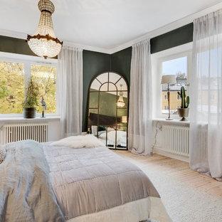 Esempio di una camera matrimoniale tradizionale di medie dimensioni con pareti verdi e parquet chiaro