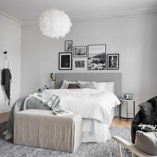 Diseño de dormitorio principal, escandinavo, grande, sin chimenea, con paredes grises y suelo de madera clara