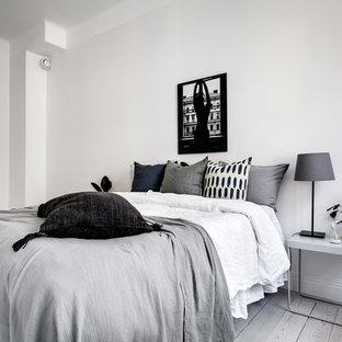 Bild på ett mellanstort minimalistiskt gästrum, med vita väggar, ljust trägolv och grått golv